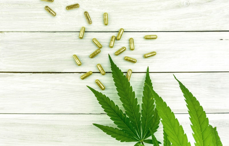 Canva CBD Pills. Group of Clear CBD Cannabidiol Capsules on Bright Wooden Backdrop with Hemp Leafs