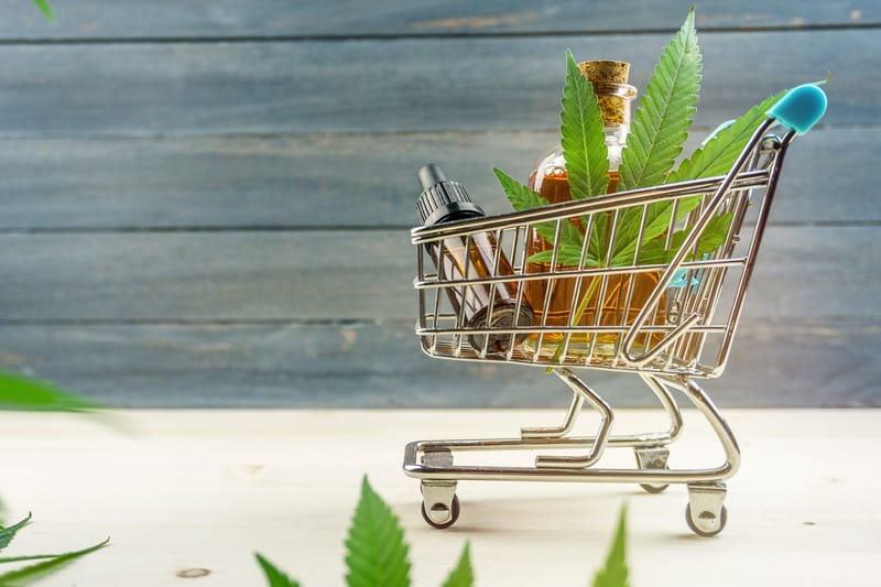 Canva Supermarket Trolley with Marijuana Leafs and Medical Cannabis Oil Cbd on Wooden Backdrop